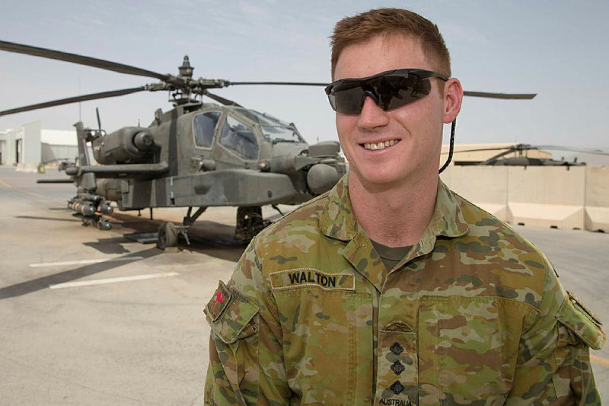 Australian Army officer, Captain Patrick Walton, of Train Advise Assist Command – South, with an AH-64 Apache attack helicopter of Task Force Panther while deployed on Operation Highroad to Kandahar Airfield in Afghanistan.