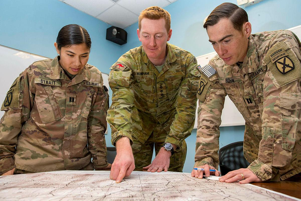 Australian Captain James Kingham, centre, conducts map reconnaissance at the Kandahar Airfield with other members of the Train, Advise, Assist Command – South future planning operations team US Army Captains Victoria Strait, left, and Eric Bohn.