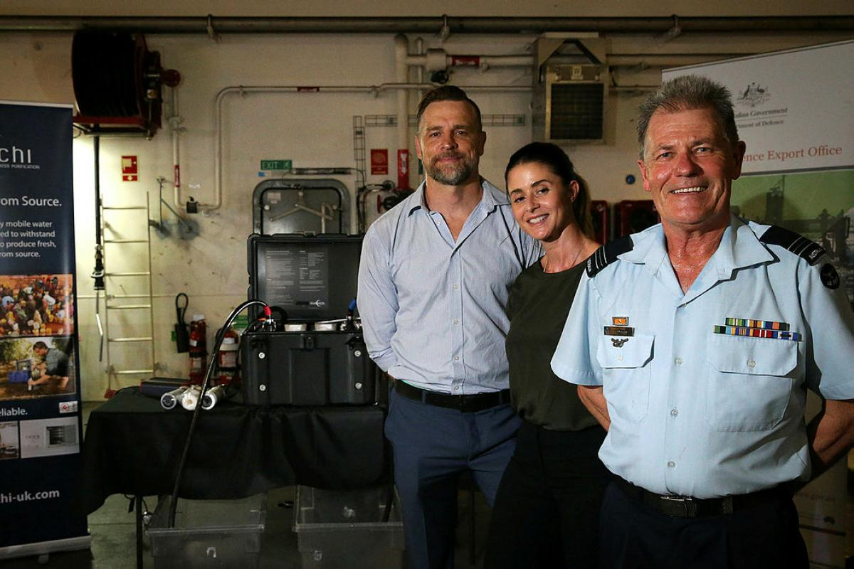 Squadron Leader Steven Rae with Andy and Zoe Cullen, the owners of Wananchi Mobile Water Purification, at the HMAS Canberra Defence Industry Expo in Singapore during Indo-Pacific Endeavour 2019. Photo: Corporal Kylie Gibson