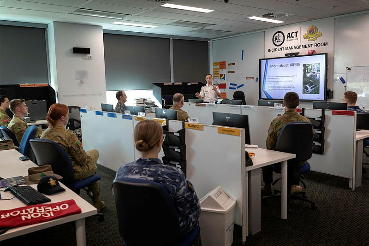 ADF personnel discuss the Australasian Inter-Service Incident Management System during Operation COVID-19 Assist at the Emergency Services Agency building in Fairbairn, Canberra. Photo: Corporal Sagi Biderman