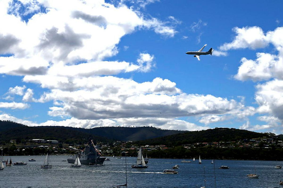 An Air Force P-8A Poseidon aircraft conducts a flypast over HMAS Hobart on the River Derwent during the 2021 Royal Hobart Regatta. Photo: Warrant Officer Class 2 Max Bree