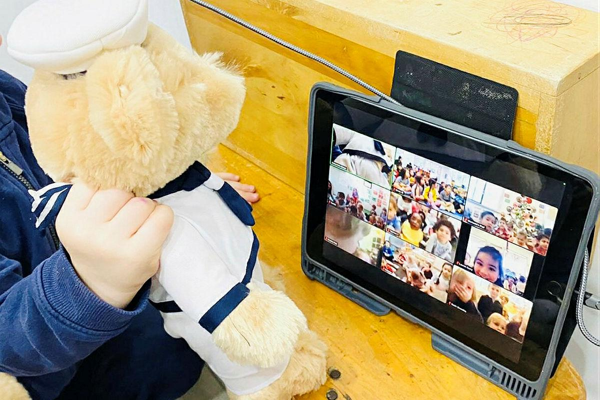 A Navy teddy is held by a child from the Vaucluse Cottage Childcare Centre in Sydney, during a Zoom call to sister preschools. Photo: Emma Wholihan