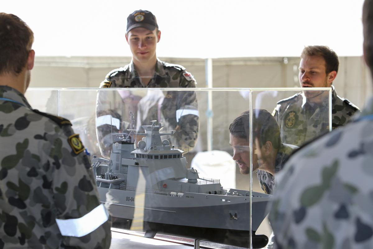 Navy personnel with a model of an Arafura class Offshore Patrol Vessel. Photo: Lieutenant Ryan Zerbe