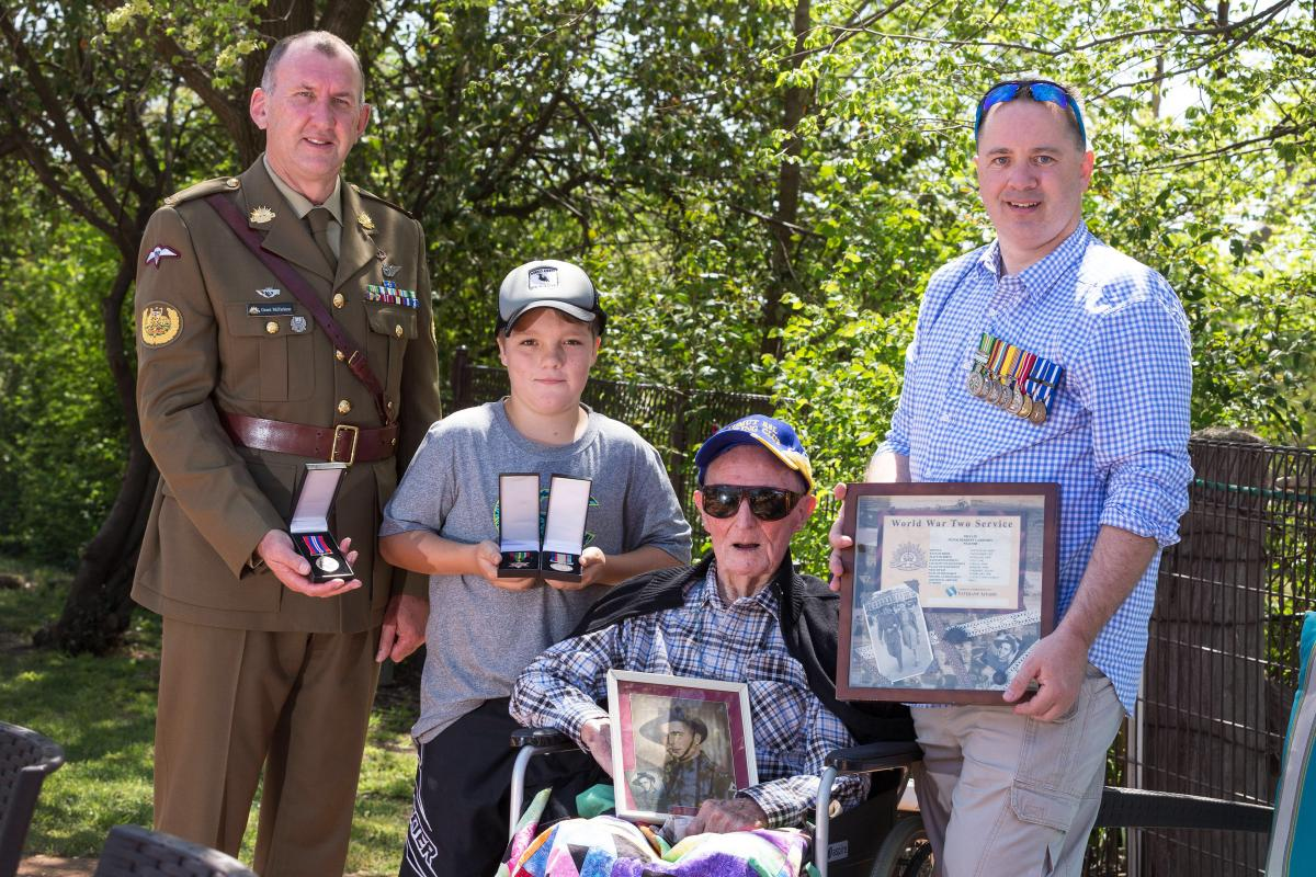 Regimental Sergeant Major - Army, Warrant Officer Grant McFarlane with World War II veteran Peter Carberry, his grandson Nathan Dean and great grandson Cody Iles with the medals and badge.