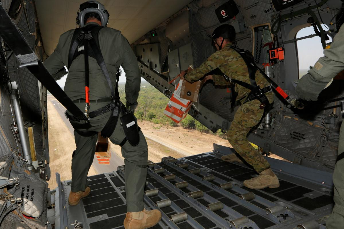 Sergeant Blake Reeve, a loadmaster with Air Force's No. 35 Squadron, and Private Ryan Cheevers, an air dispatcher from Army's 176 Air Dispatch Squadron, launch heliboxes out of a C-27J Spartan during an air drop into Kowanyam. Photo: Corporal Colin Dadd