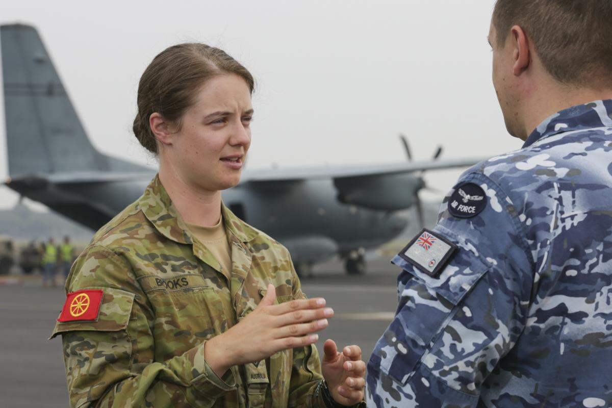 Army Corporal Ashton Brooks, from the Joint Movement Control Office, liaising with an Air Force member during the dispatch of  supplies. Photo: Corporal Kylie Gibson