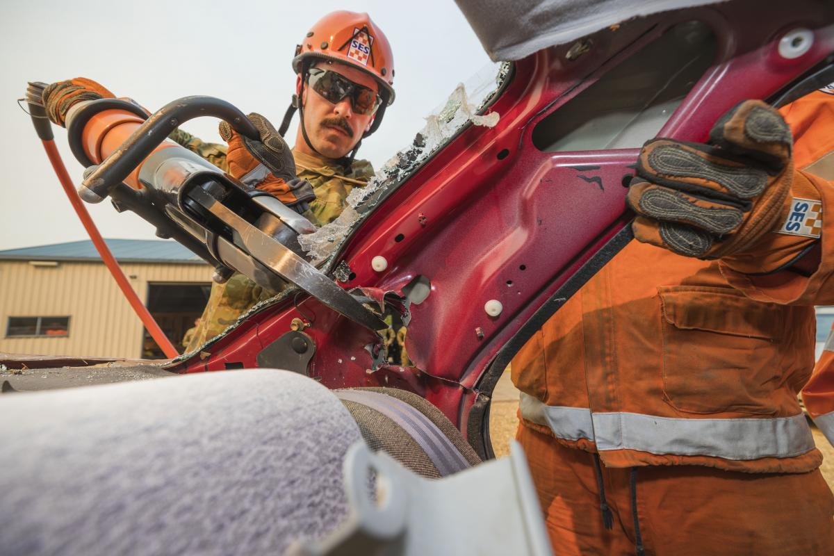 Private Andrew Cuttler, of the 5th/6th Royal Victorian Regiment, helps a State Emergency Service volunteer use the 'jaws of life' during training at the Bright SES depot. Photo: Private Sebastian Beurich
