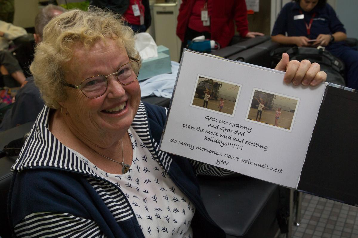 Maureen Jewell with the photo book created by her granddaughters detailing their experiences during the bushfires. Photo: Leading Aircraftman John Solomon