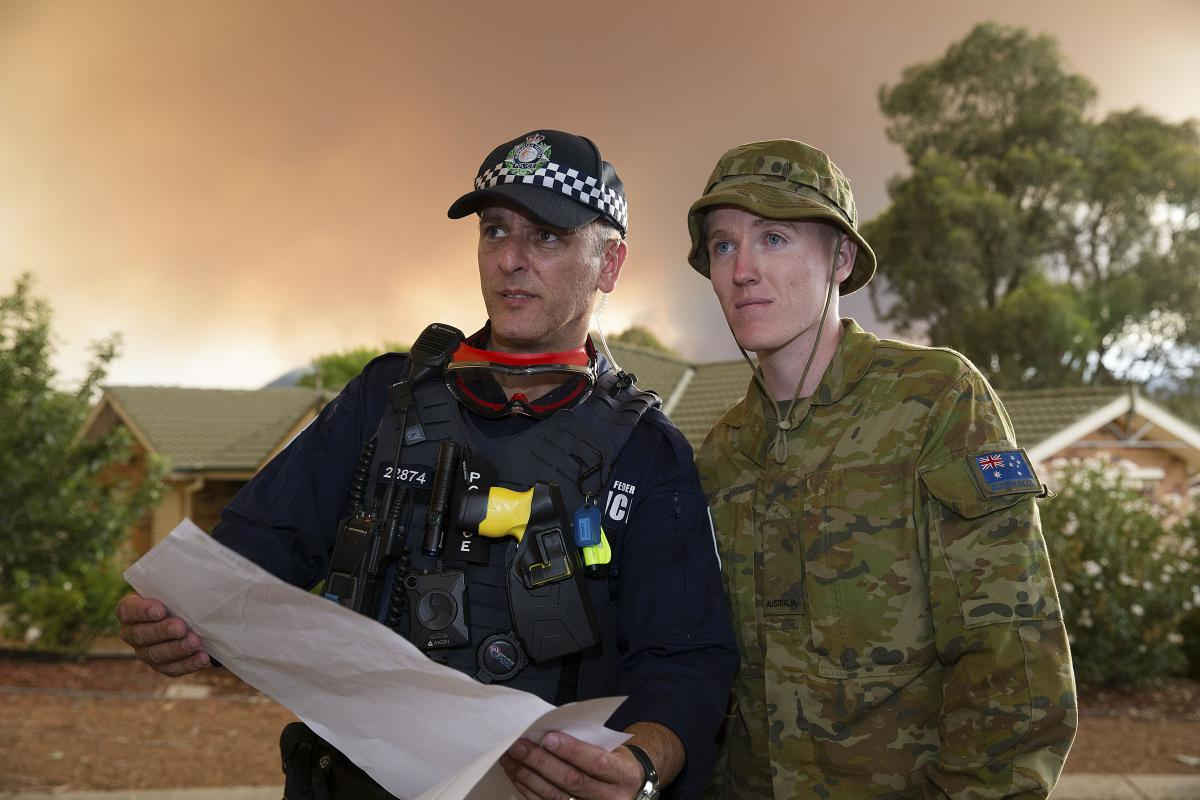 Private Lleyton Jones and Australian Capital Territory policeman Constable Marko Banic about to begin door-knocking in Canberra's southern suburbs to advise of the Orroral Fire in Namadgi National Park. Photo: Sergeant Max Bree