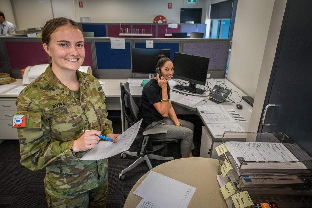 Private Rachael Byrne, from the 11th Combat Service Support Battalion, and Olivia Colley, from the Discharge Management Unit in Brisbane, call civilians in quarantine. Photo: Trooper Jonathan Goedhart