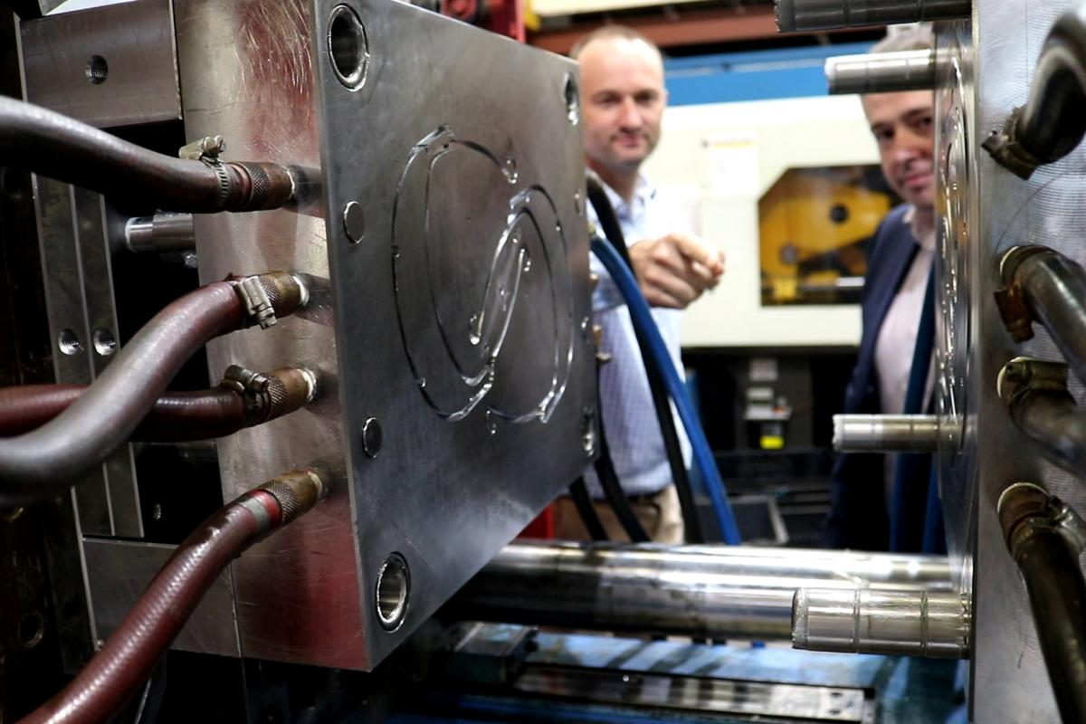 Jim Grose, left, Managing Director of Axiom, and Ben Barona, from DST, observe the injection moulding die being used to produce face shield headbands. Photo: David Kilmartin