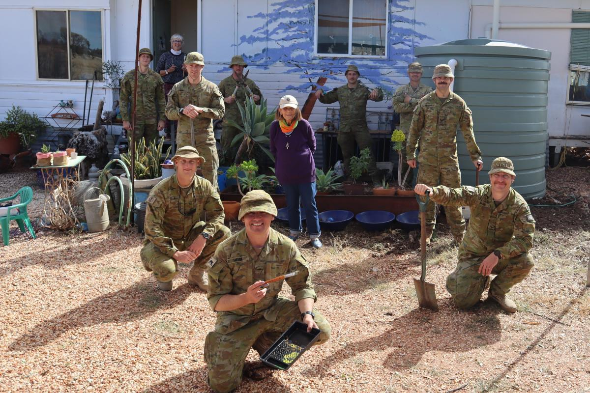 Soldiers of 6 Battalion Royal Australian Regiment with Mrs Ellis after finishing some yard work at her home. Photo: Chaplain Stan Fetting