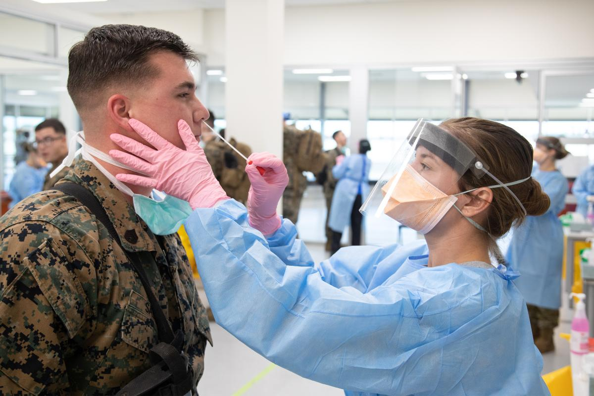 A Royal Australian Navy Medic from ADF Joint Health Unit - Central Australia takes a swab as part of pre-quarantine health screening for recently arrived US marines at RAAF Base Darwin. Photo: Petty Officer Peter Thompson