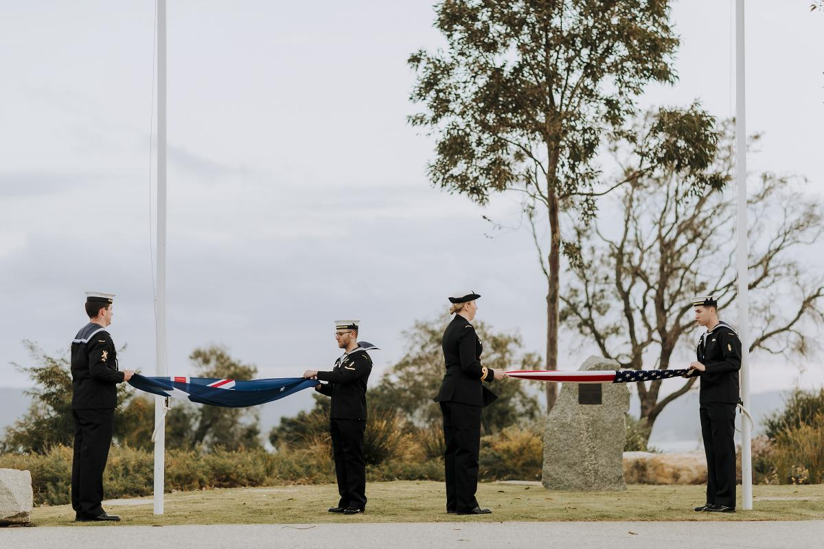 Members of HMAS Farncomb ship's company fold the national flags of Australia and the United States at the memorial event held in Albany, Western Australia. Photo: Lee Griffith