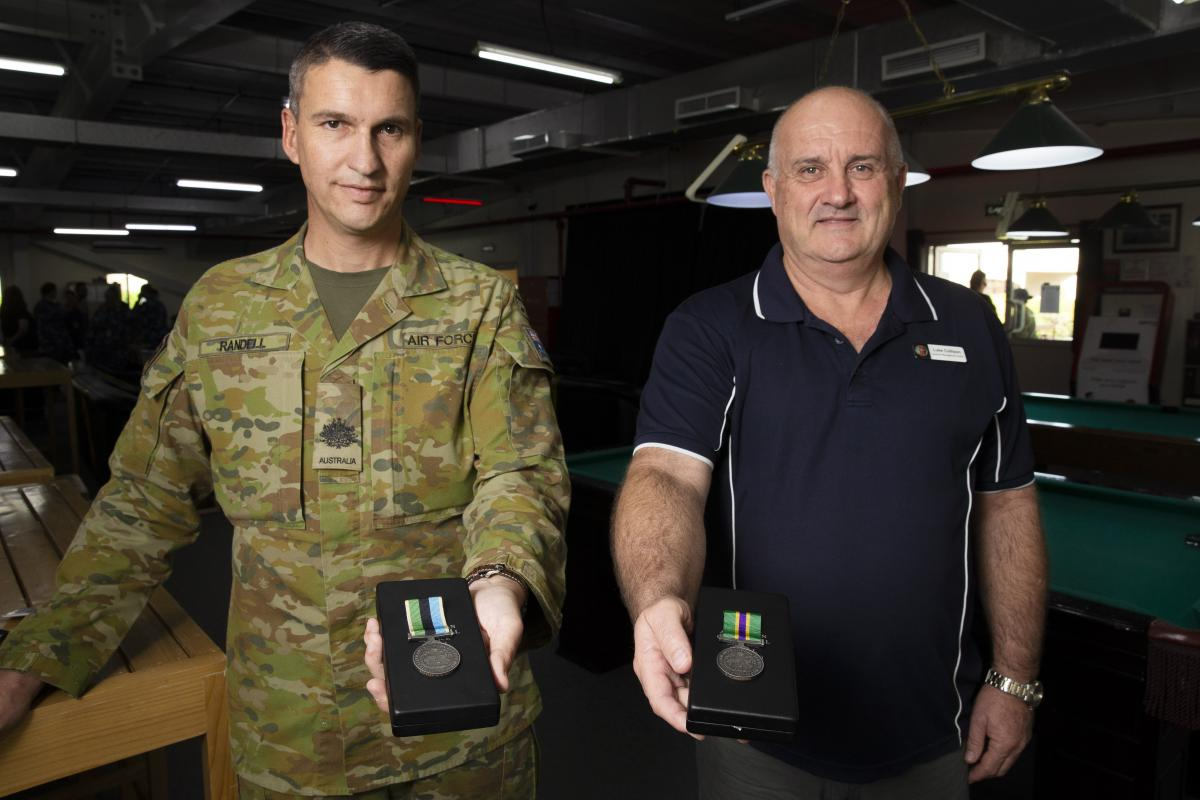 Warrant Officer Class 1 Jason Randell, left, and Luke Collison display their respective military and civilian Australian Operational Service Medals at Australia's main operating base in the Middle East region. Photo: Corporal Tristan Kennedy
