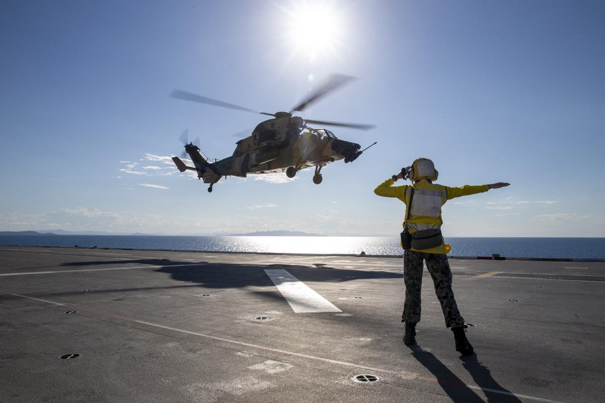 Able Seaman Lily Hardin waves off an Army ARH-Tiger as it takes off from the deck of HMAS Adelaide near Townsville during Exercise Sea Wader. Photo: Leading Seaman Nadav Harel