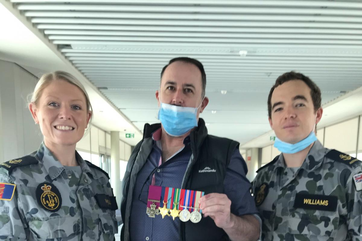 Leading Seaman Alisha Mosely and Leading Seaman Alan Williams with Terrance Quinn, the great-nephew of Ordinary Seaman Edward 'Teddy' Sheean, VC, and the replica medals at Brisbane Airport.