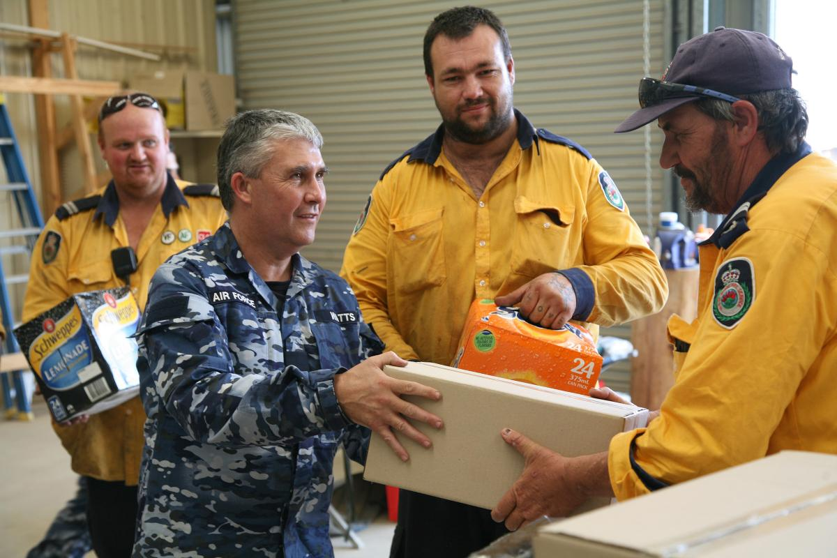 Corporal Shane Watts, a plumber from 65 Squadron at RAAF Base Richmond, delivers boxes of meals and soft drinks to RFS volunteers working out of Tumbarumba. Photo: Major Cameron Jameison