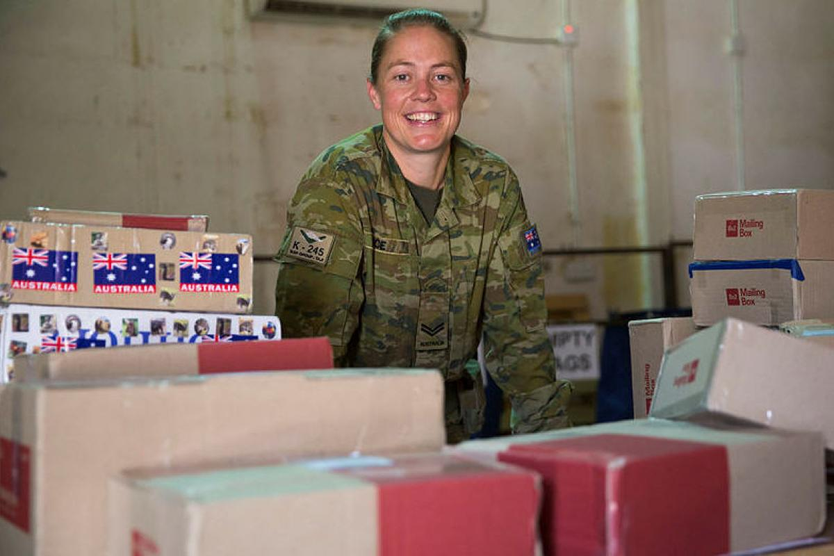 Task Group Taji postie Australian Army soldier Corporal Cassandra Rice is surrounded by work in the mail room at the Taji Military Complex, Iraq.