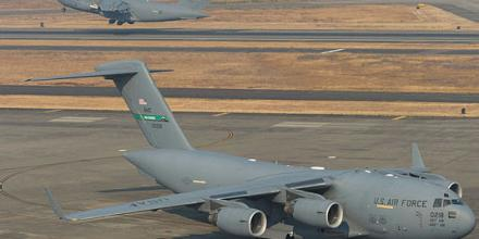 A C-17A Globemaster III from No. 36 Squadron takes off on another mission during Exercise Mobility Guardian 17, while a United States Air Force C-17A Globemaster waits on the flightline at Joint Base Lewis-McChord, Washington.