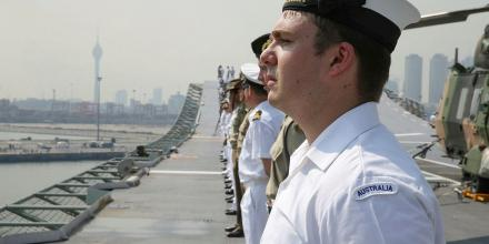 Royal Australian Navy sailor Seaman Combat Systems Operator Geoffrey Green stands with members of ship's company and ship's Army detachment on the flight deck of HMAS Canberra as it enters the port of Colombo, Sri Lanka.