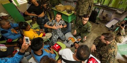 Lieutenant Christian Aca-Ac (centre) and Armed Forces of the Philippines officer Captain Henedino Vergara (centre-right) demonstrate cardio pulmonary resuscitation Pagasa Elementary School, Orani, Philippines.