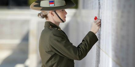 Private Hannah Bailey places a poppy at the Lone Pine memorial wall. The walls adorning the memorial carry the names of 4,228 Australian's missing, as well as those who died on hospital ships and were buried at sea. Photo: Andrew Dakin