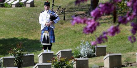 Leading Aircraftman Robert Scott, from the Royal Australian Air Force Band, plays the bagpipes at his great-great-uncle's grave site. Photo: Petty Officer Andrew Dakin