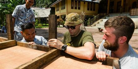 Captain Eric Brown (centre), Seaman Sam Bridger and Lieutenant Commander Haizad work to rebuild a marriage hut during a visit to the Meh Mari Cultural Village in Malaysia. Photo: Leading Seaman Steven Thomson