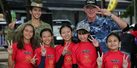 Lieutenant Jennifer Hassett and Commander Joint Task Force 661 Air Commodore Richard Owen with junior members from the Phuket Lifeguard Club