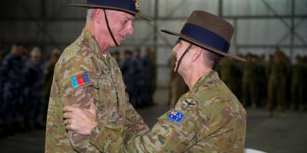 Outgoing Commander Joint Task Force 633 Air Vice-Marshal Joe Iervasi, right, promotes Commodore Mark Hill to the rank of Rear Admiral at the Transfer of Authority parade at Australia's main operating base in the Middle East.