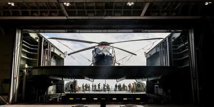 A Royal Australian Navy MRH90 helicopter being moved from the hangar to the flight deck onboard HMAS Canberra during Exercise Talisman Sabre 2019. Photo: Able Seaman Leo Baumgartner