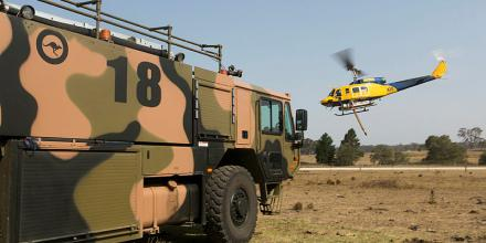 Air Force fire fighters from No. 22 Squadron provide fire protection to firefighting helicopters as they conduct hot-refuelling operations at Mittagong Airfield, NSW. Photo: Sergeant Christopher Dickson