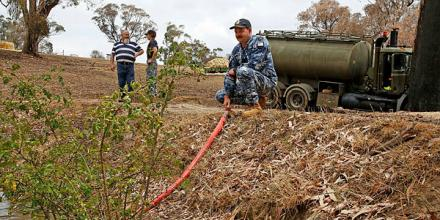 Air Force Leading Aircraftman Corrie Street, of No. 65 Squadron, RAAF Base Richmond, offloads 15,000 litres of much-needed water to farmer Rod Daisley of Tumbarumba, New South Wales. Photo: Sergeant Dave Morley