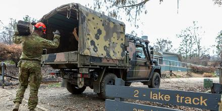 Corporal Travis Ward from the 6th Battalion, Royal Australian Regiment, loads a G-Wagon with debris at the Eurobodalla Regional Botanic Gardens, NSW. Photo: Corporal Dan Pinhorn