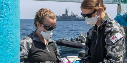 Lieutenant Maree Altham, left, and Lieutenant Shannen Rowe from HMAS Toowoomba conduct tests on a parcel discovered after boarding and searching a dhow in the Gulf of Aden. Photo: Leading Seaman Richard Cordell