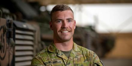 Private Oliver Atkinson Perillo in front of protected mobility vehicles at Australia's main operating base in the Middle East. Photo: Petty Officer Yuri Ramsey