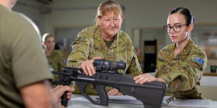 Warrant Officer Class 2 Cheryl Peebles, centre, with a soldier signing out a weapon from the armoury at Camp Baird in the Middle East region. Photo: Corporal Tristan Kennedy