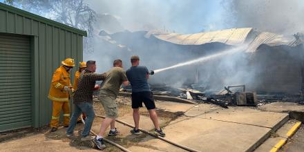 Combined Arms Training Centre soldiers Major John Ozols, left, Major Matt Whitwell and United States Marine Corps Gunnery Sergeant Ryan Accornero help firefighters battle a blaze at Puckapunyal Primary School on December 6 last year.
