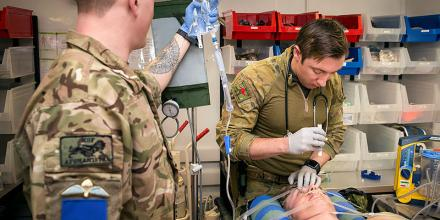 Australian Army medic Corporal Robert Jinkinson, right, checks a casualty's vitals during a simulated medical training exercise at Camp Qargha. Photo: Leading Seaman Craig Walton. This image was taken prior to social distancing requirements.