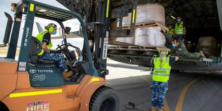 Forklift driver Leading Aircraftwoman Sophie Berthelot, Leading Aircraftwoman Angelina Prountzos and Warrant Officer Adam Olding unload fire retardant from an Air Force C-17A Globemaster at Busselton airport. Photo: Leading Seaman Richard Cordell