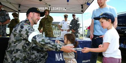 Leading Seaman Jackson Cashion hands sunglasses to Isabella, 2, and Benjamin Devenish, 6, at the Defence Force Recruiting tent during the 2021 Royal Hobart Regatta. Photo: Warrant Officer Class 2 Max Bree