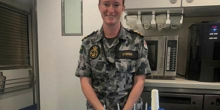 Commanding Officer Australian Defence Vessel Cape Inscription Lieutenant Commander Jessica O'Brien with a cake made by the catering crew. The crew was awarded the Silver Platter Award ─ Minor War Vessel.
