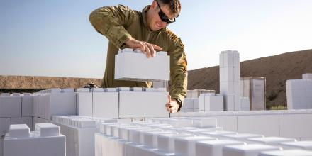 A soldier with Task Group Taji, works on installing a new modular urban training facility on Camp Taji.