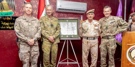 NZ Army officer Colonel Ben Pitt, Rear Admiral Mark Hill, Iraqi Security Forces officer Colonel Shehab Nasser and British Army officer Major General Gerald Strickland in front of the final operating capability certificate.