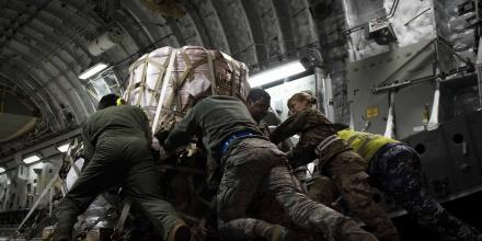 United States Air Force and Royal Australian Air Force personnel push a pallet of fire suppressant up the ramp of an Australian C-17 Globemaster at Nellis Air Force Base, Nevada. Photo courtesy of the United States Air Force.