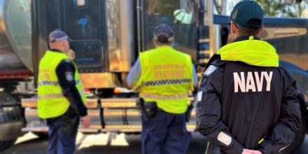 A sailor assists NSW Police at a border control point on the Princes Highway South of Eden.