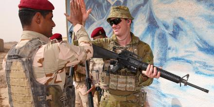 Australian Army trainer Captain Anthony Davis high-fives an Iraqi Army soldier after completing urban warfare drills at the Taji Military Complex.