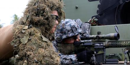Leading Aircraftman Andrew Lawson (left), provides advice and guidance on how to fire a sniper rifle to a Japan Air Self-Defence Force security force member as part of Exercise Cope North, Andersen Air Force Base, Guam.