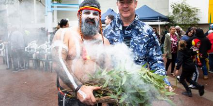 Worimi man Justin Ridgeway stands with Senior Australian Defence Force Officer RAAF Base Williamtown Group Captain Peter Cluff during a NAIDOC Week event in Raymond Terrace.